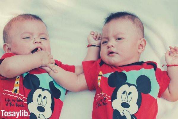 two babies wearing red mickey mouse shirts lying on the bed