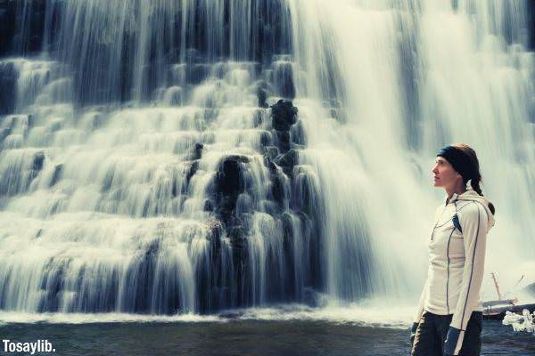 woman in white jacket long hair standing in front of waterfalls
