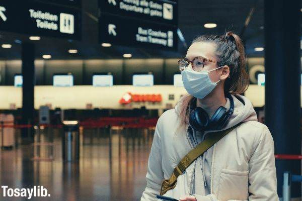woman wearing facemask with headphones hanging on neck