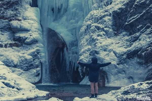 person looking at ice frozen waterfall while spreading arms wide
