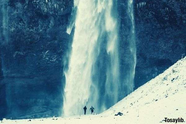 two people walking on ice time lapse photo of flowing waterfall