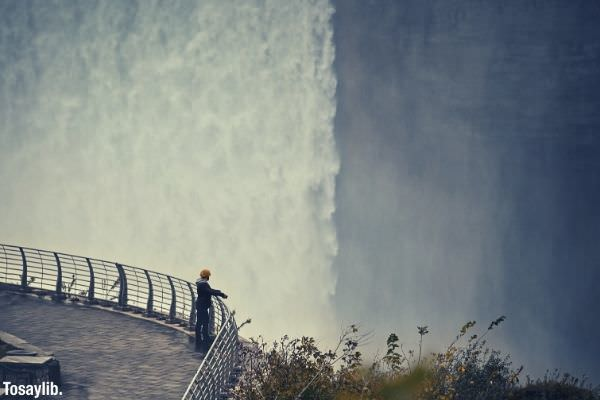 man standing fence concrete floor near edge beside waterfall