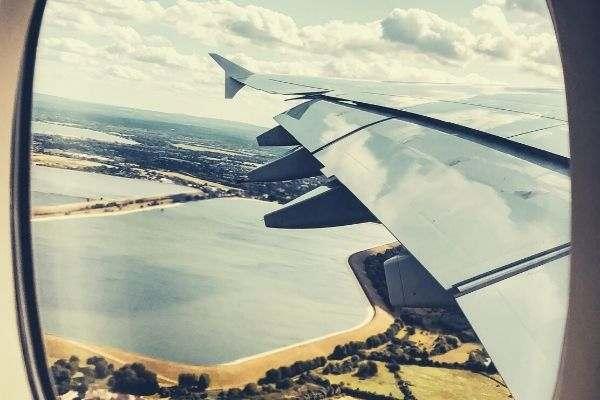 airplane-window-seat-view-flight-sky-and-field