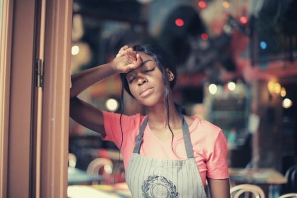 shallow focus of a woman wearing pink shirt sick day work leaning at the door
