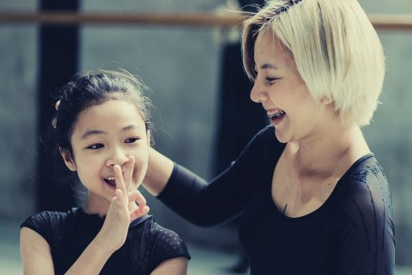 short-haired-woman-in-black-color-outfit-touching-girls-head-ballerina-sitting-on-the-floor-other-ways-to-say-I-agree