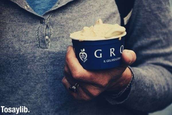 person wearing gray sweater holding grom ice cream