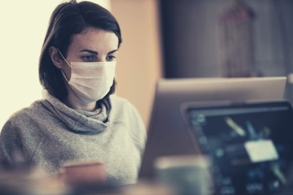ask for pay raise pandemic woman in gray hoodie wearing white mask looking at the monitor