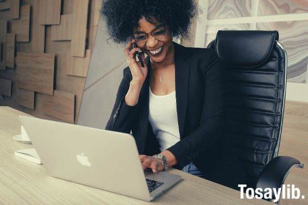 woman in black blazer sitting on black office chair using smart phone smiling