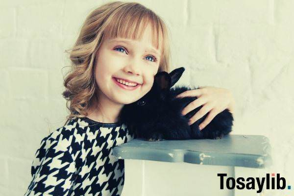cute girl with blue eyes holding a black rabbit on top of gray wood surface