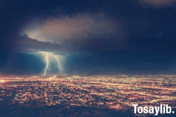 aerial shot of buildings with light mountain silhoutte lightning dark sky clouds