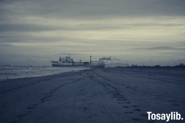 grayscale photo of beach with ship on the sea gray skies