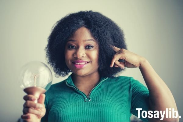 positive young african american lady holding light bulb in hand on gray background