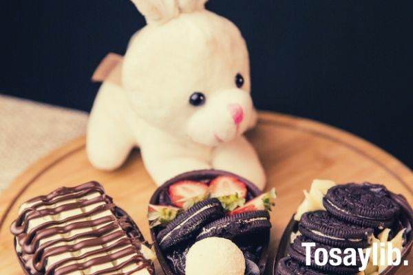 cute plush toy rabbit behind the chocolates on top of round wooden board