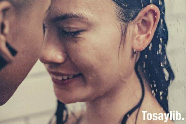 multiracial naked couple having shower together smiling