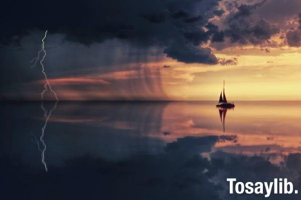 silhouette photography of boat on water during sunset going inside the dark clouds storm with lightning