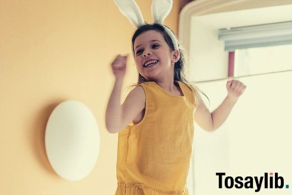 girl in yellow top and white pants with rabbit ears headband jumping on top of bed