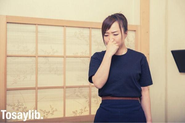 staff wearing a black uniform pinching her nose