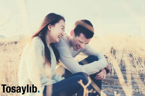 man and woman laughing during daytime