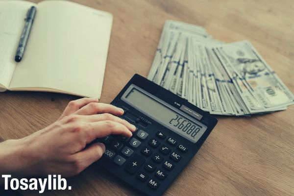person holding black desk calculator dollar bill notebook