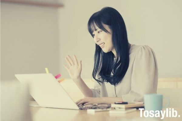 a woman waving towards a computer screen while sitting in front of laptop
