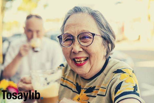 smiling elderly woman while drinking chocolate sitting outside