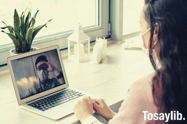 woman wearing pink jacket using her laptop on video call distant learning