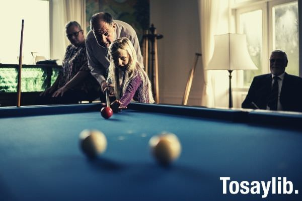 small girl playing pool with her grandpa old elderly