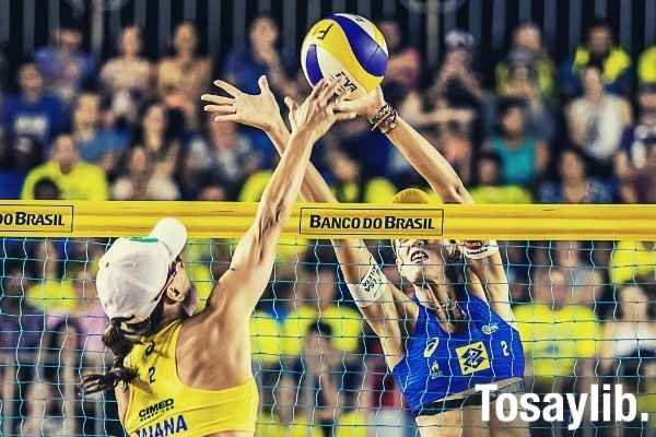 two woman playing volleyball yellow and blue net banco do brazil