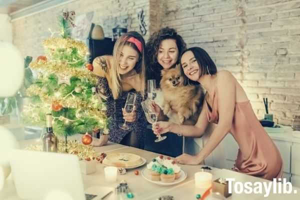 three women having a party while on video call holding wine glass