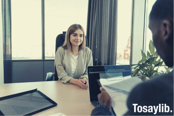 woman in white long sleeve shirt sitting beside brown wooden table job interview