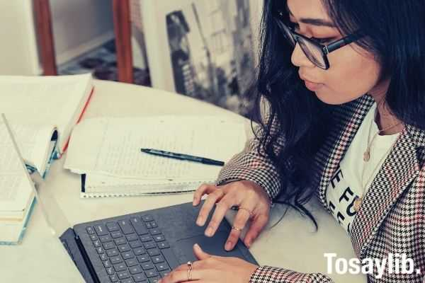 woman in red and white plaid using laptop wearing eyeglasses