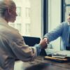 feature-ethnic-businessman-shaking-hand-of-applicant-in-office-answer-why-want-to-work-here-question