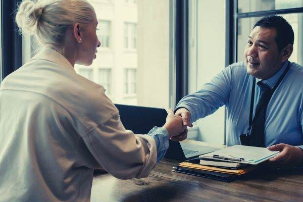 ethnic businessman shaking hand of applicant in office answer why want to work here question