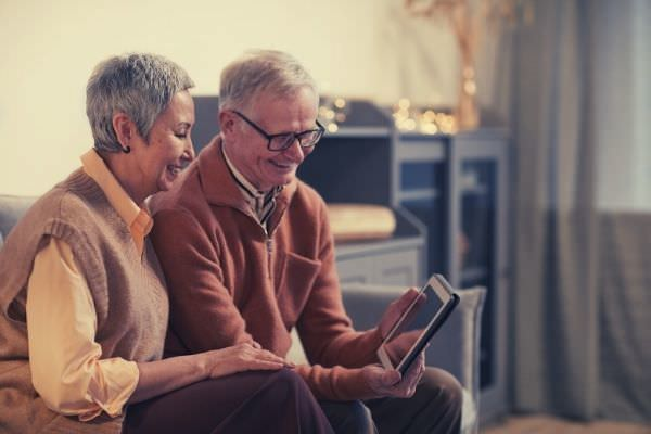old-couple-smiling-while-looking-at-a-tablet-words-to-describe-elderly