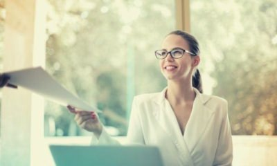 positive-businesswoman-doing-paperwork-in-office-smiling-ask-previous-employer-for-reference