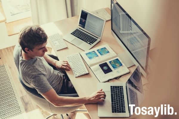 man using three computers researching