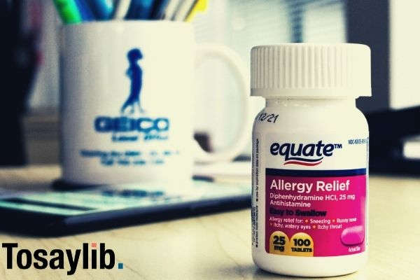 equate allergy relief tablet bottle on wooden table with smartphone