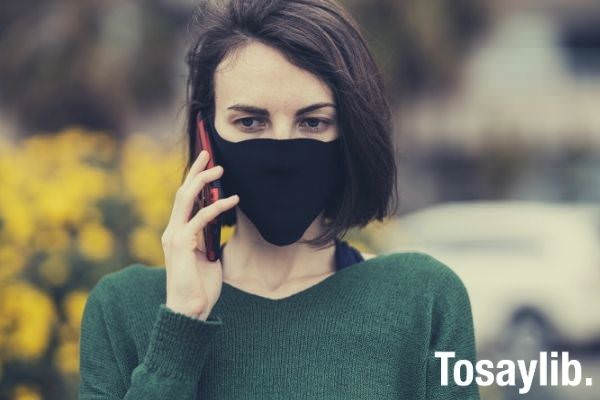 woman in green sweater with black mask holding smartphone