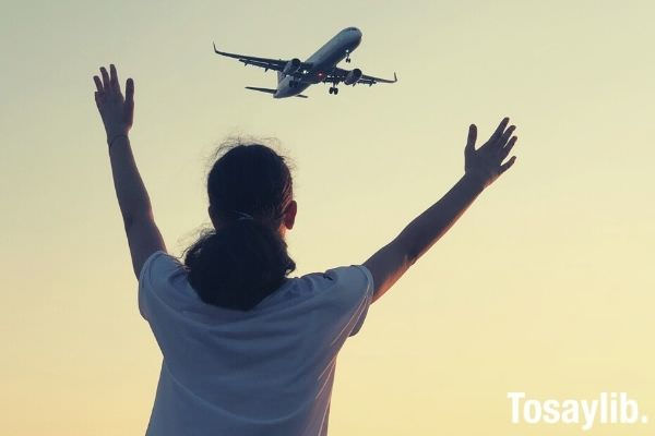 woman in white shirt waving her hand on airplane