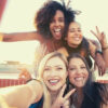 cheerful-young-diverse-women-showing-peace-sign-while-taking-selfie-on-rooftop-words-to-describe-laughter