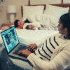 mother-using-laptop-near-baby-sleeping-on-bed-with-father-excuses-not-to-work-night-shift