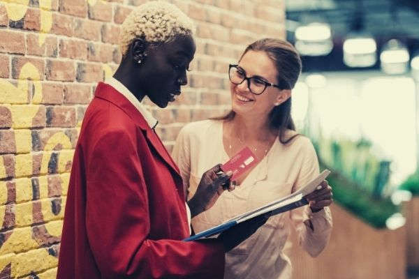 multiethnic-businesswomen-discussing-payment-with-credit-card-brick-wall-words-to-describe-work-ethic