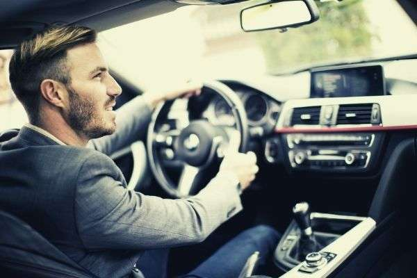 young man driving modern car looking at the rear view mirror