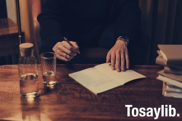 person in black long sleeve shirt holding white paper writing