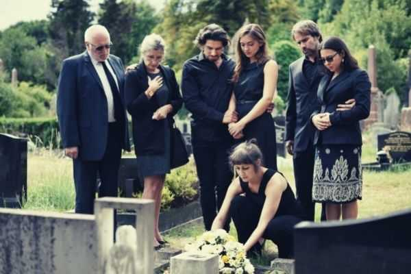 family laying flowers on grave