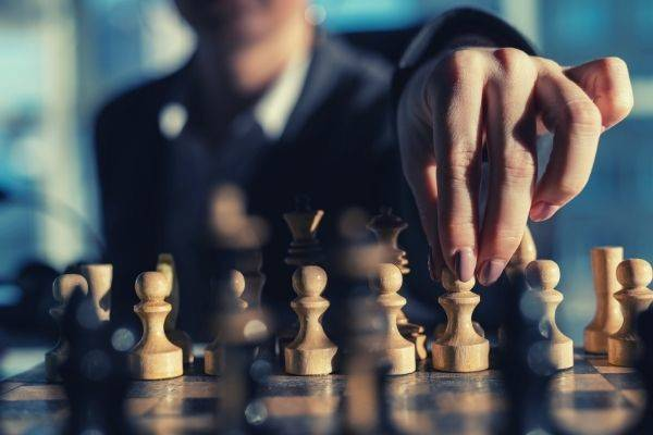 business woman hand wearing suit playing chess close up photo