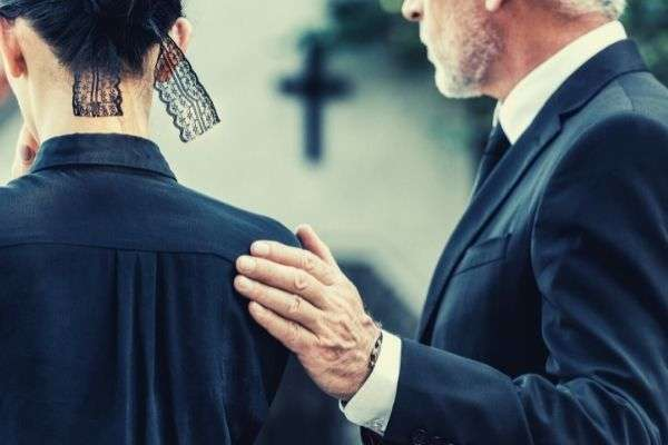 cropped view man touching woman mourning black attire