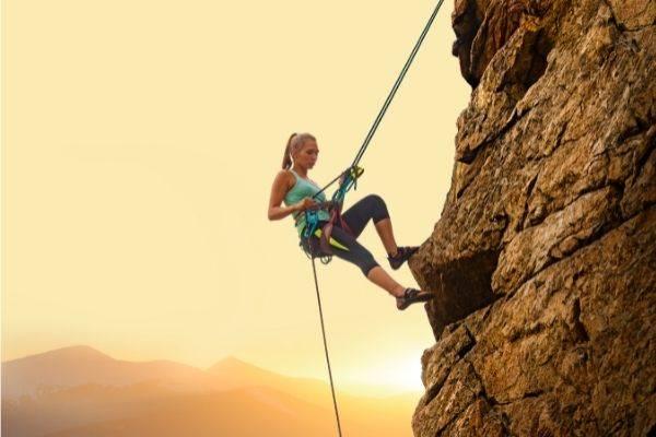 beautiful woman climbing on high rock yellow sun