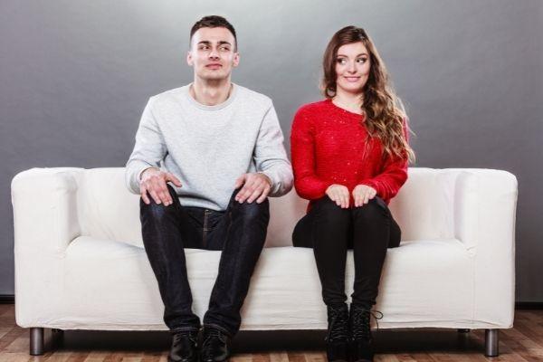 shy woman man sitting on sofa red sweater