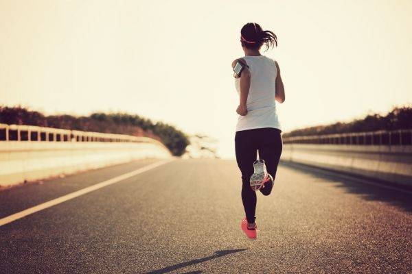 young fitness sport woman running on paved road sunset